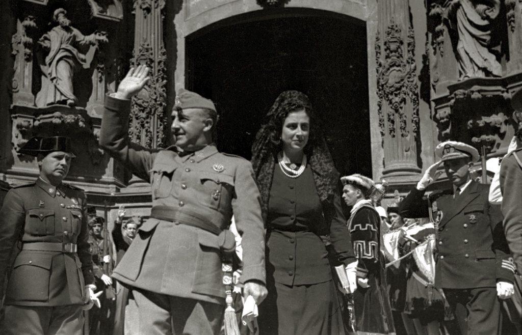 Francisco Franco in uniforme con accanto la moglie, sfila davanti a militari e prelati. Il 28 marzo del 1939 iniziava il suo regime.