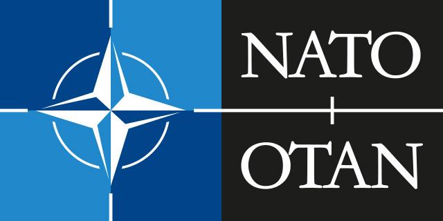 Una rosa dei venti bianca campeggia in azzurro e blu, accanto, sue due barre nere sono riportate le due grafie NATO e OTAN per il Patto Atlantico