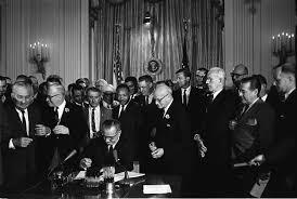 Lyndon B. Johnson, seduto su una scrivania, firma la legge sui diritti civili, circondato dai senatori. Alle sue spalle, un uomo afroamericano sorride.