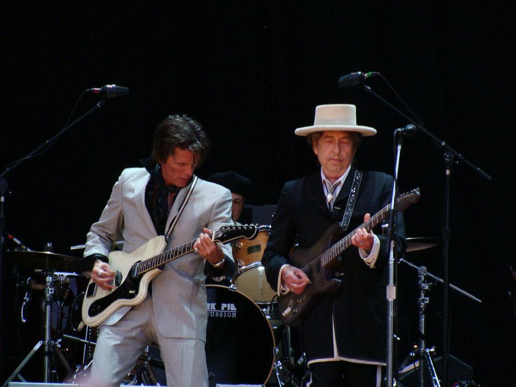 Bob Dylan suon la chitarra durante un concerto, accanto il suo fedele bassista.