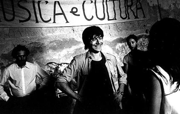"""Alcuni ragazzi sorridenti in uno scatto in bianco e nero, alle loro spalle uno striscione con su scritto """"Musica e Cultura"""". In primo piano Peppino Impastato"""