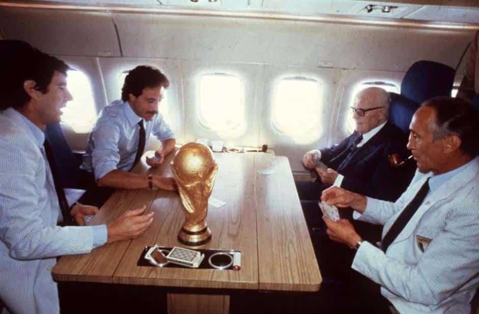 Italia Campione del Mondo: Il presidente Sandro Pertini, i calciatori Causio e Zoff Italian e il CT Enzo Bearzot giocano a scopone sul volo di ritorno. Sul tavolo la coppa del mondo.