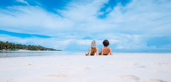 In spiaggia è importante proteggersi dai raggi UV usando creme solari.