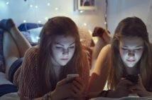 Due adolescenti concentrate sui loro smartphone e sui loro social network di sera prima di andare a dormire (credits: DigitalWellbeing)